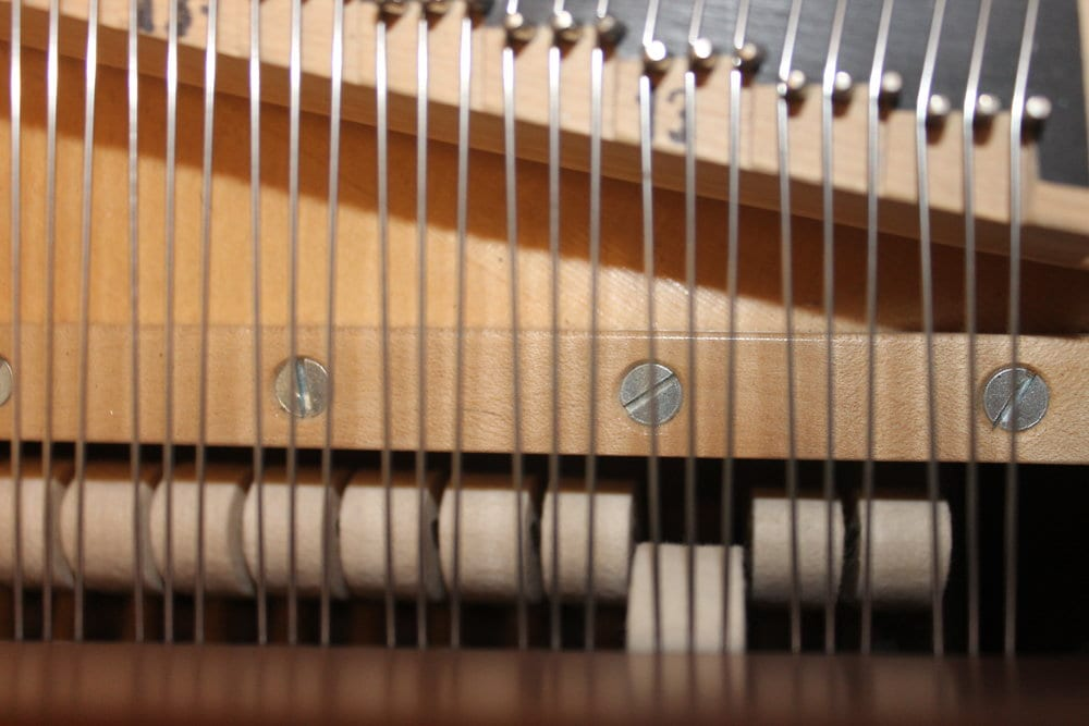Spacing the hammers to the strings. There is no one standard for spacing; some technicians will place the hammer so it only strikes two strings when the shift pedal is engaged, others will place it where the hammer still strikes all three strings, just on a different part of the hammer.